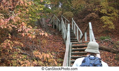 Fall stairs - A young man climbs a big flight of stairs in...