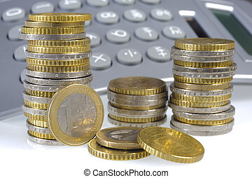 stacked euro coins and financial calculator