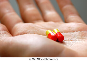Taking pills Hand with two capsules