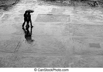 Alone in the rain - Two women with umbrella walking in rain