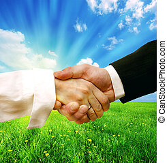Business handshake on nature background concept