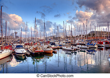 Boats in the harbor of Barcelona, Spain at sunset
