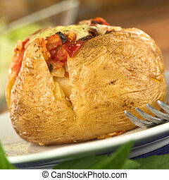 Baked potato with tomato filling and cheese on top Selective...