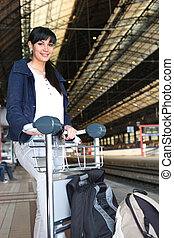 Young woman pushing a luggage trolley on a train platform