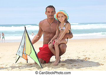 Man and little girl playing with kite at the beach