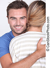30 years old man hugging a woman, her face is not visible on...