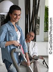 a young woman vacuuming at a senior woman's home