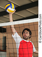 Volleyball player pushing ball over net
