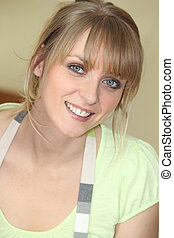 Young blonde woman in an apron