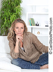 Serious woman sitting crossed legged on a white sofa
