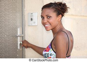 young metis woman  opening a metallic door