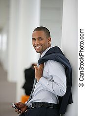 Attractive businessman leaning against wall with his jacket...