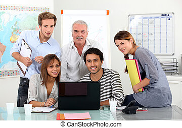 Young team of people sitting around a laptop with an older...