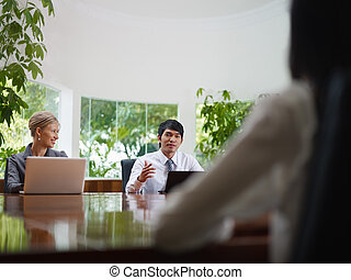 business man and woman talking in meeting room - Young...