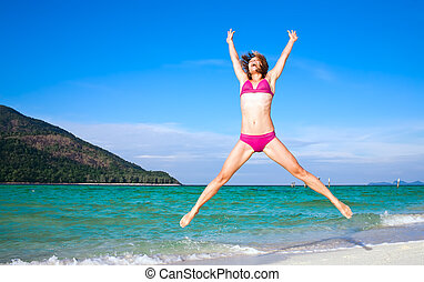 Beach fitness - Happy woman jumping on a tropical island...