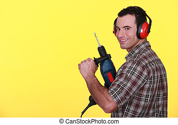 Man wearing protective ear muff and holding power drill