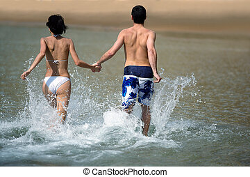 Couple running through the water