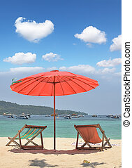 A red beach umbrella and chaise lounges - Tropical paradise...