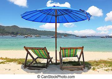 A blue beach umbrella and striped chaise lounges - A...