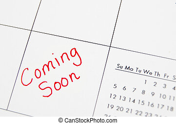 """Closeup of a calendar with """"Coming Soon"""" text in  red"""
