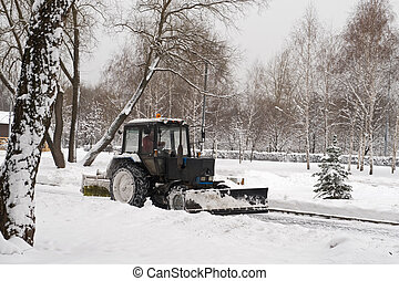 small tractor snow removal in park - winter snow removal a...