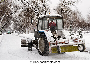 snow removal - winter snow removal a small tractor in the...