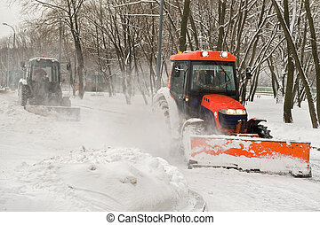 Two tractor snow removal in the park - winter snow removal a...