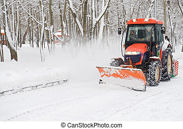 winter snow removal a small tractor in the park
