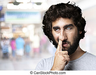 man joking - young man with finger in his nose at a crowded...