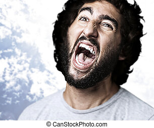 young man - portrait of young man shouting against a blue...