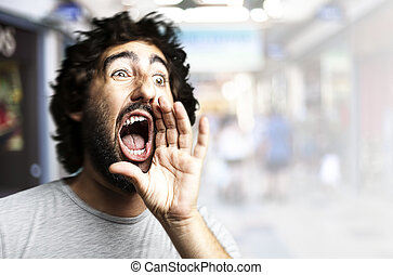 man shouting - portrait of young man shouting against a...