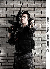 young soldier with rifle with finger up against a grunge...