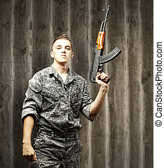 young soldier aiming - portrait of young soldier holding...