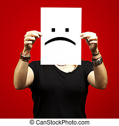woman with sad emoticon - woman holding paper with sad...