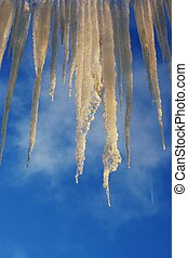 Icicles on the roof against the blue sky