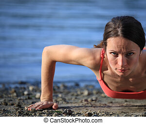 Push-ups on beach - Cute woman doing push-ups on beach. Shot...