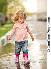 Child in puddle - Cute child walking on puddle in autumn