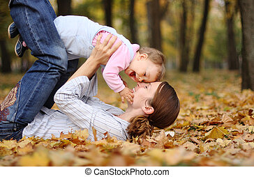 Family moments - Mum with baby have a fun in autumn park:...