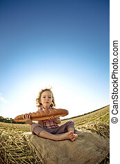 Child with bread sitting on hayrick in autumn wheat field....