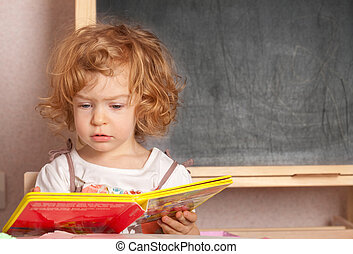 Schoolgirl reading textbook in a class against blackboard