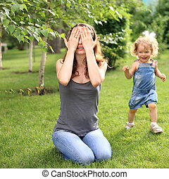 Hide and seek - Woman and child playing hide and seek in...
