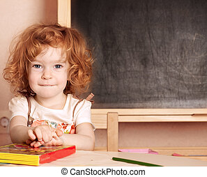 Schoolchild in a class - Funny smiling schoolchild in a...