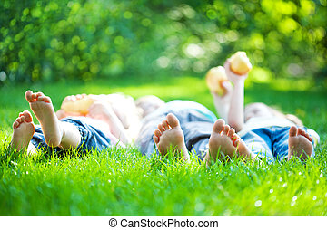 Children feet in green grass - Children laying on grass...