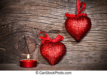 Valentine`s day - Two hearts and burning candle on old wood