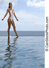 Woman stood by infinity pool