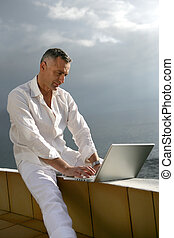 Man working on his laptop by the ocean