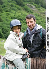 Young child learning to ride a horse