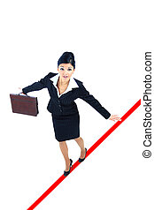 young business woman walking on a tightrope nearly falling...