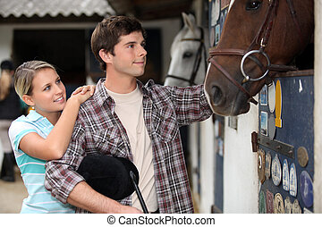 young couple in a stable