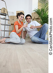 Couple sat on flooring toasting